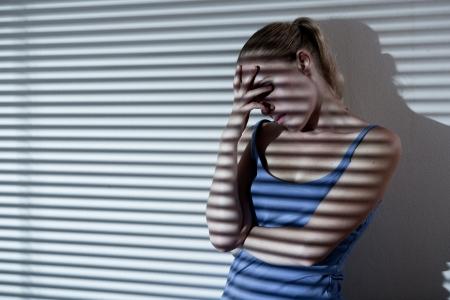 mujer llorando: Retrato de una mujer joven triste y deprimido en el ambiente depresivo raya, imagen desaturada Foto de archivo