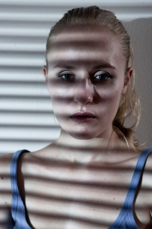 desaturated: Portrait of a unhappy and depressed young woman in depressive stripe environment, desaturated image Stock Photo