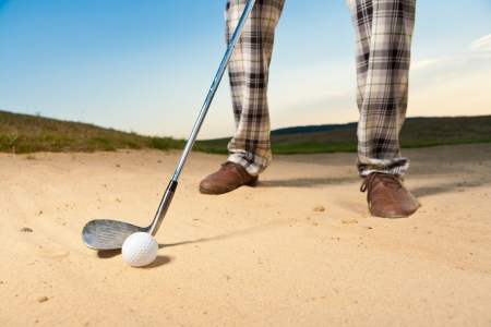 excersise: closeup shot of golf ball with golf club right before tee off from bunker