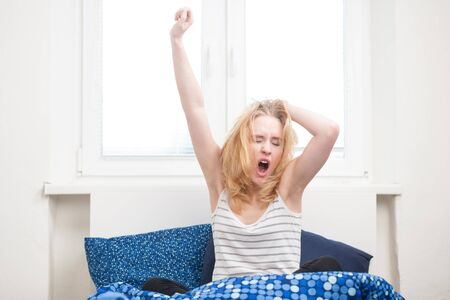 getting late: caucasian woman in bed, getting up late to work with terrible hangover, funny concept