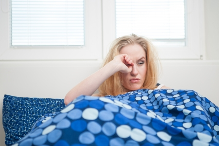 caucasian woman in bed, getting up late to work with terrible hangover, funny concept