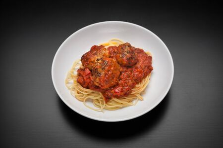 classic italian dish- spaghetti pasta with meatballs and tomato sauce on a clean, dark background Stock Photo - 18496637