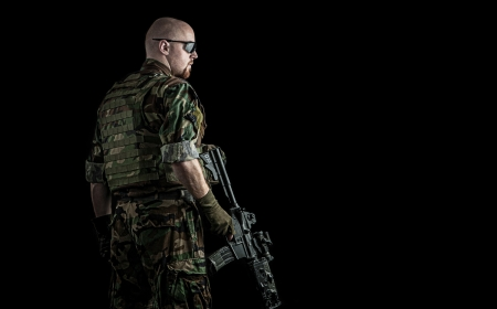 us army marine recon special forces seal team soldier holding an assault rifle gun on a black background, very dramatic and super sharp action image