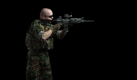 us soldier:  us army marine recon special forces seal team soldier holding an assault rifle gun on a black background, very dramatic and super sharp action image