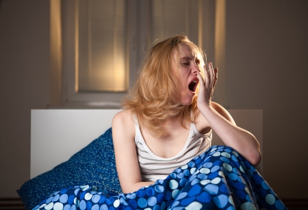 young caucasian woman in bed with headache depression and hangover from early morning waking up, everyone hates early mornings concept-