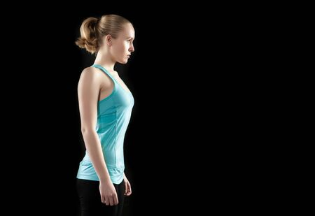 young healthy woman preparing and concentrate to begin fitness workout, black background photo