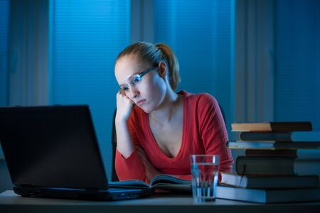 young bored female college student studying poorly at late evening before exam, funny night procrastination concept Stock Photo - 18496659