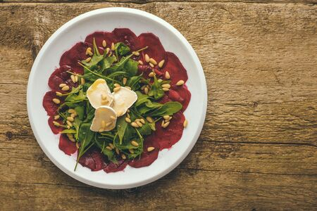 Plate of a beet carpaccio served with wild rocket, pine nuts and goat cheese on a wooden background