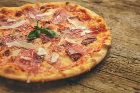 pizza with prosciutto ham, parmesan cheese and dried tomatoes  served with basil leaves on the top Stock Photo