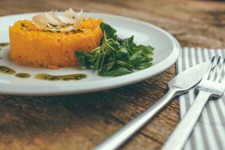 classic italian saffron risotto alla milanese served with parmesan cheese and corn salad plant