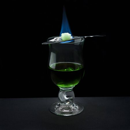 absinth shot served in bohemian way (with flaming sugar on top) on black background
