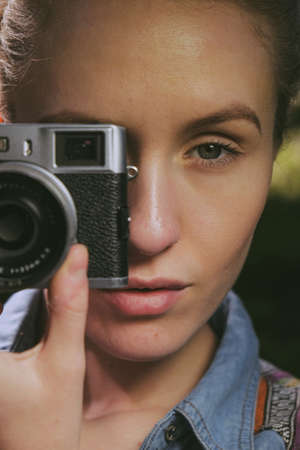 rangefinder: portrait of a young pretty woman looking through a vintage looking rangefinder camera