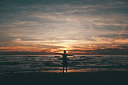 woman standing and looking at the sunset and the sea
