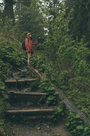 hiker walking through wilderness  in heavy rain wearing rainshell jacket