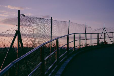 road with the fence alongside in sunset Stock Photo