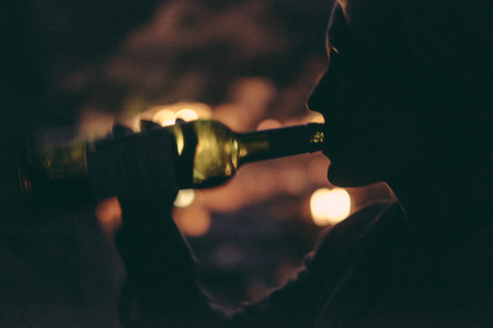woman drinking wine at night, right from the bottle Stock Photo