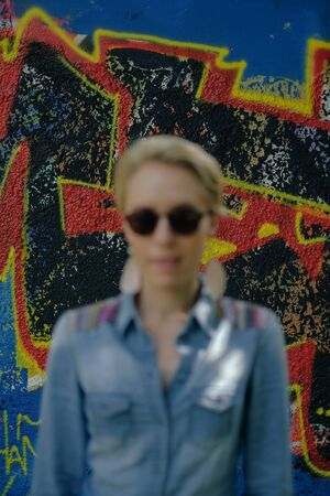 young woman with stylish sunglasses standing in front of a graffiti wall, focus is on the wall
