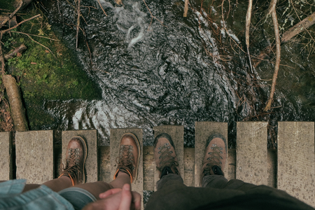 point of view of a couple of hikers with heavy boots standinh on the bridge across mountain brook
