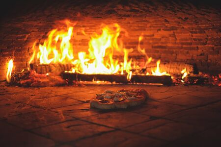 homemade pizza in the simple owen with fire in the backgorund Stock Photo