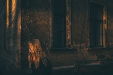 lonely woman sitting in a streak of light surrounded by old building environment Stock Photo
