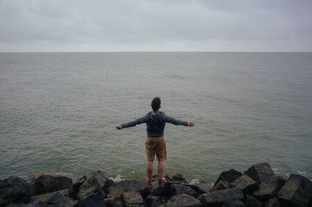 backview of young man screaming at the empty sea