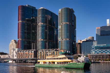 BARANGAROO, SYDNEY, AUSTRALIA - July 19, 2019: Ferry at Barangaroo, Darling Harbour day scene, new development in downtown Sydney on waterfront with boats, restaurants, bars, skyline, and high rise
