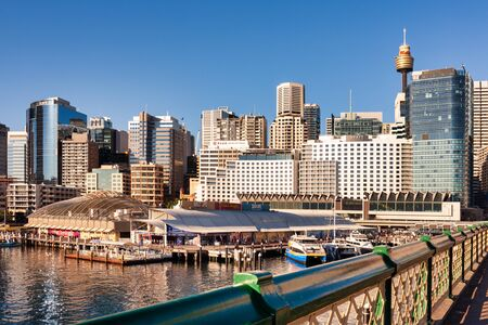 DARLING HARBOUR, SYDNEY, AUSTRALIA - July 19, 2019: Darling Harbour, Downtown Sydney, Sydney Aquarium, Sydney Tower, Ferry on waterfront from Pyrmont bridge day scene on sunny blue sky afternoon Editorial
