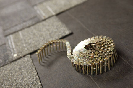asphalt shingles: A coil of roofing nails on a new roof in progress