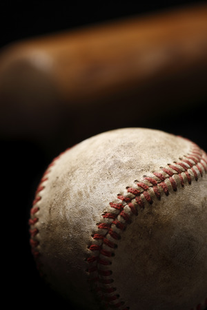 A close-up of a weathered baseball with a bat in the background Reklamní fotografie