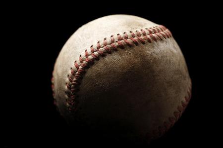 A worn baseball with a black