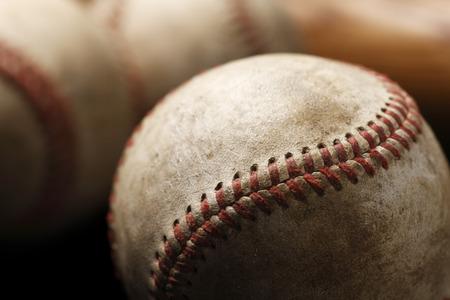 A moody image of weathered baseballs and a bat