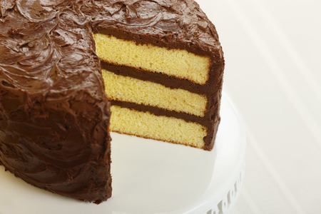 chocolate icing: A yellow layer cake with chocolate icing with a slice missing
