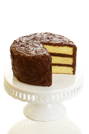 A yellow layer cake with chocolate icing with a slice missing