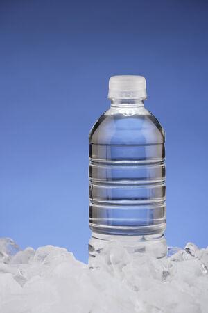 vetical: Una botella de agua en el hielo con el fondo azul.