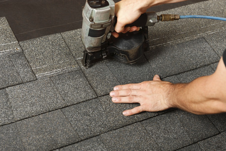 roofer: Applying roof shingles with a roofing gun