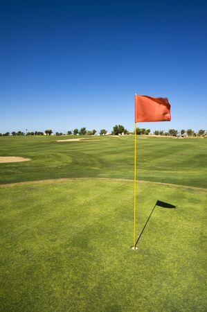 The green of a golf course with a flag in the hole Stock Photo
