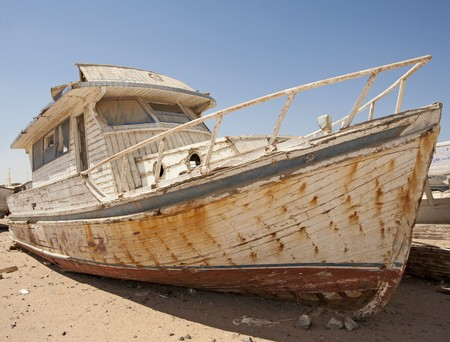 An abandoned derelict wooden boat in the desert photo