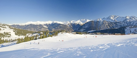 piste: Panoramic view over a piste at ski resort with mountains in background