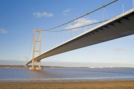 Large suspension bridge spanning a wide river on a clear day Standard-Bild