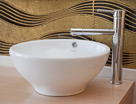 washbasin: Washbasin in a bathroom with tap on a wooden shelf