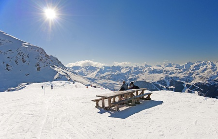 Two skiers sat at picnic table relaxing on piste
