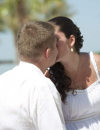 A young newly married couple sharing a romantic kiss Stock Photo - 9460318