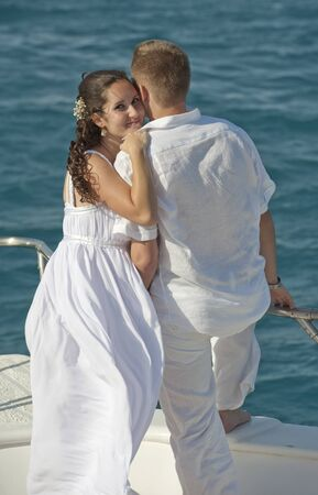 Newly married couple embracing while stood on the bow of a boat