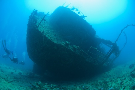Scuba divers exploring the stern section of a large shipwreck in the sun Stok Fotoğraf
