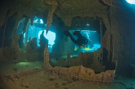 Scuba divers exploring a large shipwreck Stock Photo - 10085256