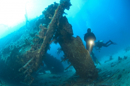 ship wreck: Scuba divers exploring the stern section of a shipwreck in the sun Stock Photo