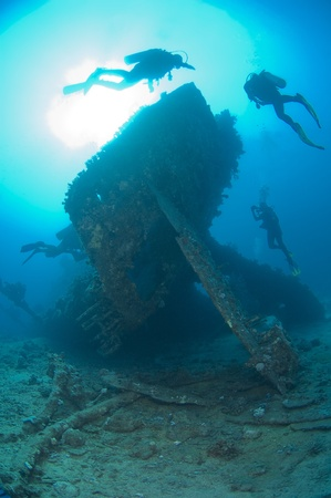 explore: Scuba divers exploring the stern section of a shipwreck in the sun Stock Photo