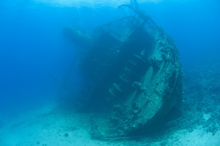 Stern section of a large underwater shipwreck on the seabed listing to port