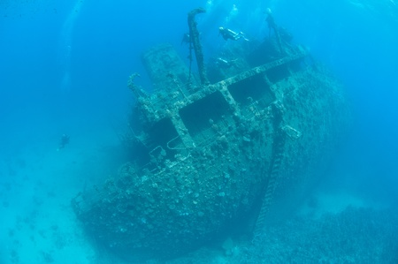 Scuba divers exploring the stern section of a large shipwreck