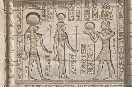 Hieroglyphic carvings on the exterior walls of an ancient egyptian temple photo